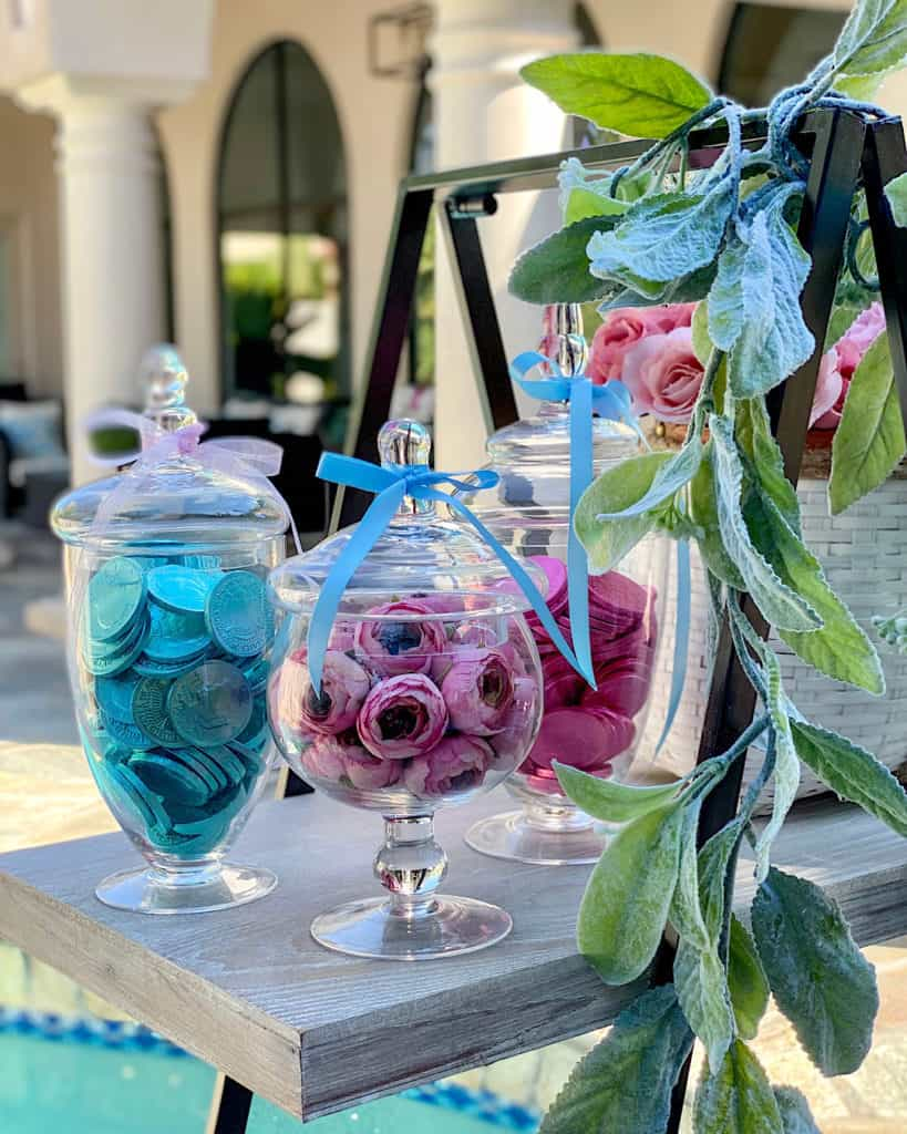 Pink and blue candy and flowers in glass display jars