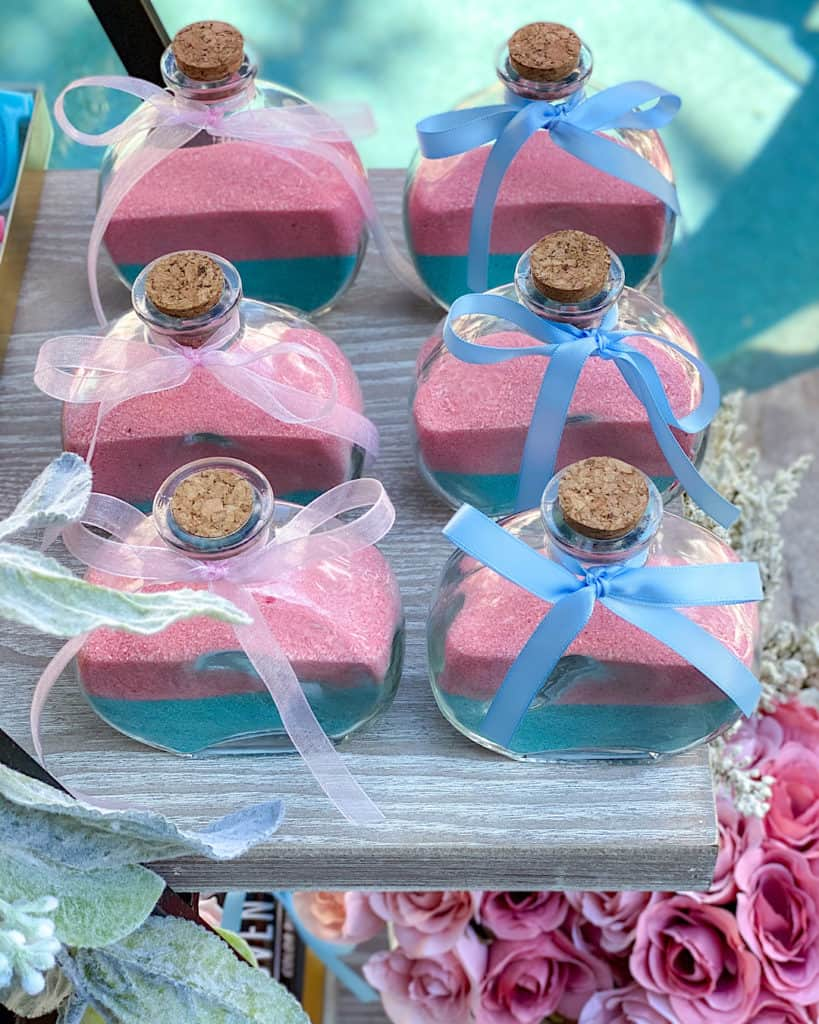 Glass bottles with pink and blue sand and ribbons