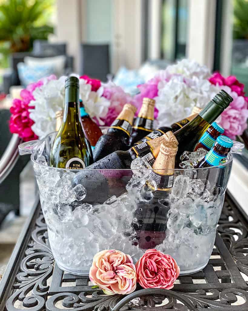 Beer and wine in an ice bucket with pink white and blue flowers