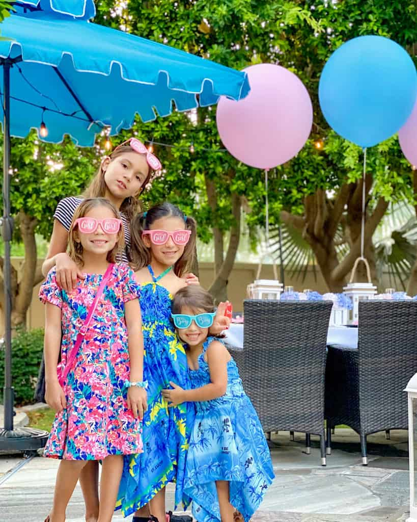 Girls in pink and red dresses at a gender reveal party