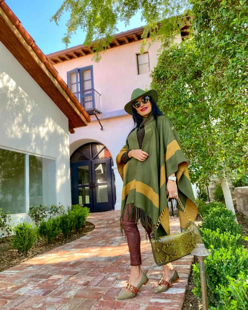lady in green poncho and brown trousers with green bag. Fall fashion 2021